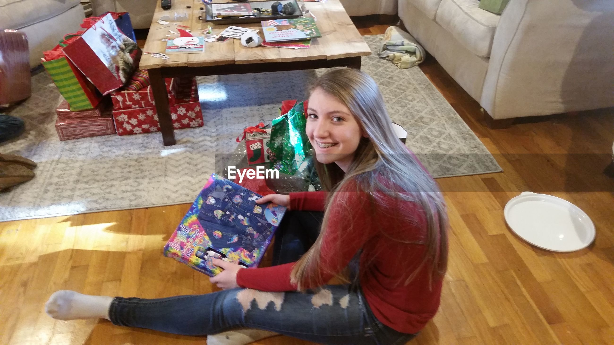 High angle portrait of happy teenage girl reading book while sitting at home during christmas
