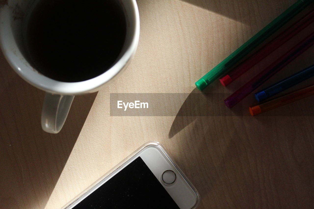 High angle view of coffee and mobile phone with pens on table