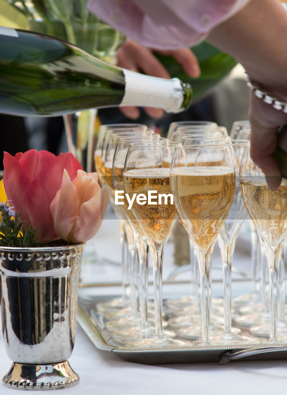 Cropped image of man pouring champagne in glasses on table