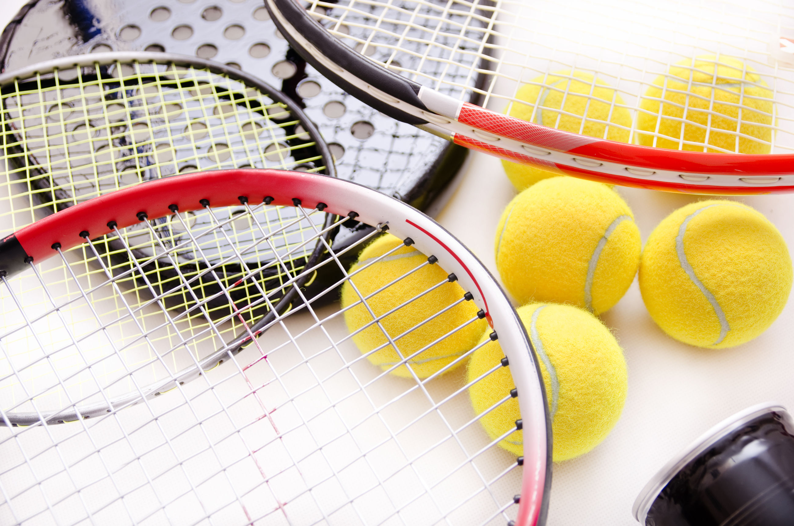 Close-up of tennis rackets and balls on white background