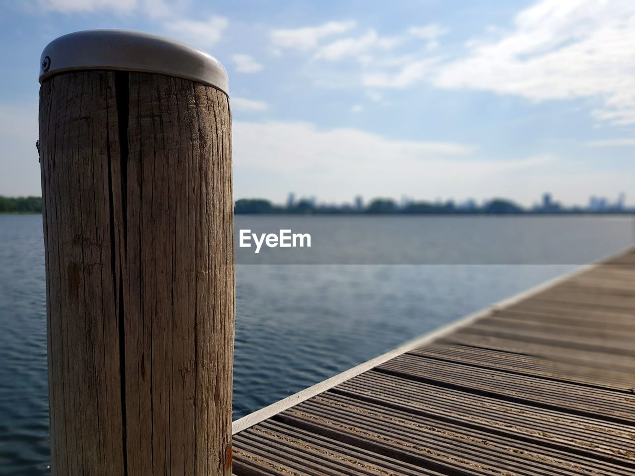 water, wood - material, sky, lake, focus on foreground, post, no people, nature, wooden post, day, cloud - sky, tranquility, tranquil scene, pier, outdoors, scenics - nature, beauty in nature, non-urban scene, close-up