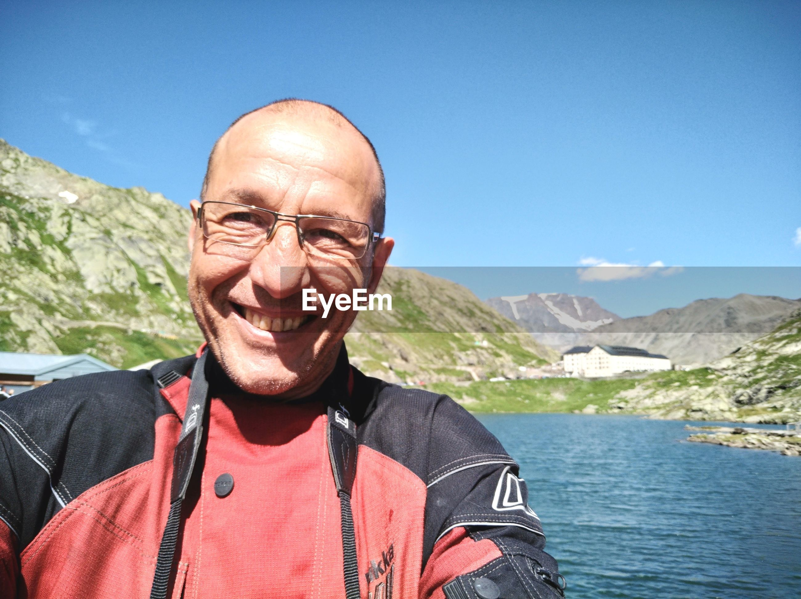 Portrait of smiling mature man standing by lake against blue sky