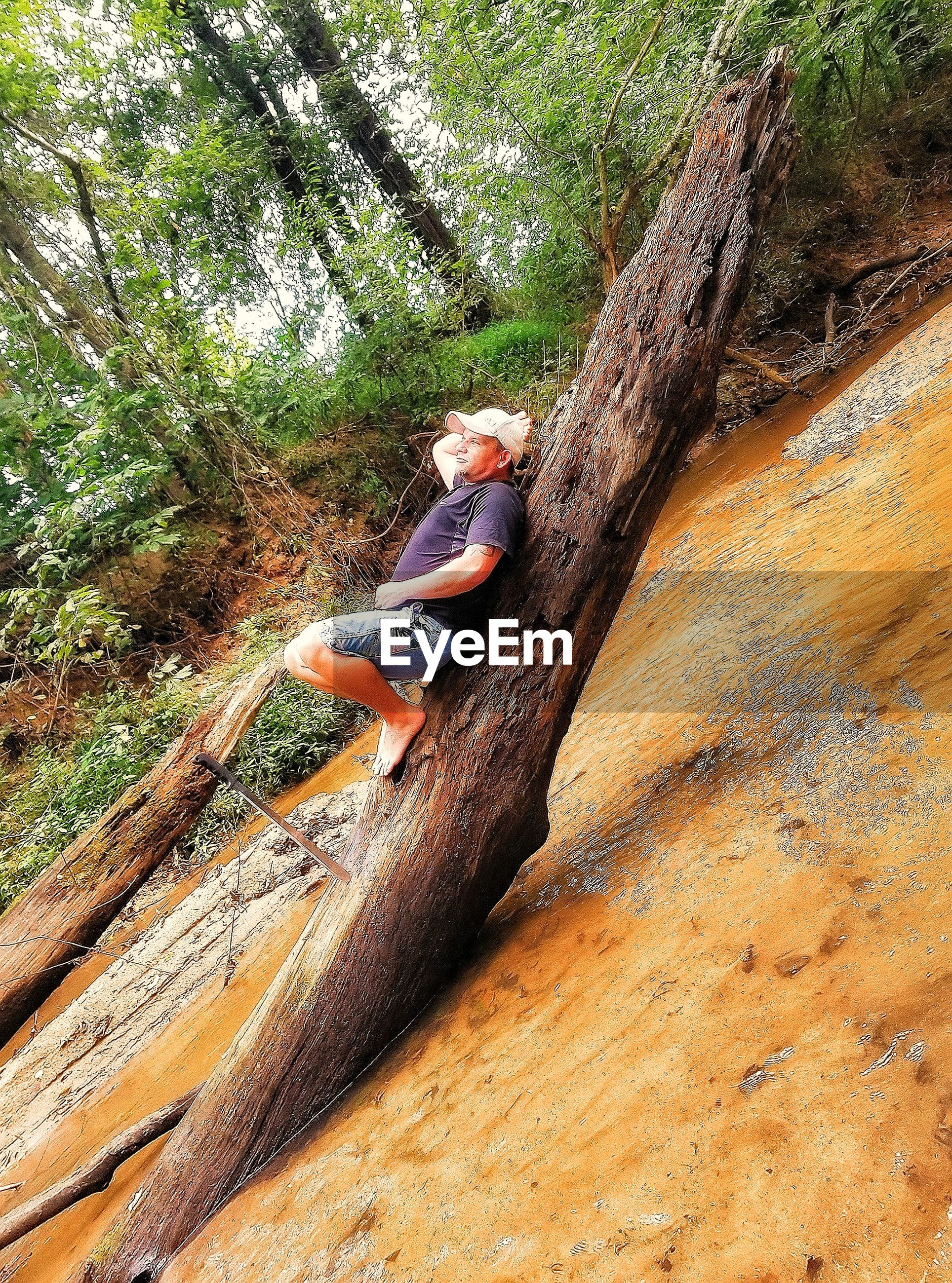 full length, tree, one person, leisure activity, day, real people, risk, nature, rock - object, casual clothing, adventure, outdoors, rock climbing, lifestyles, climbing, young adult, beauty in nature, people