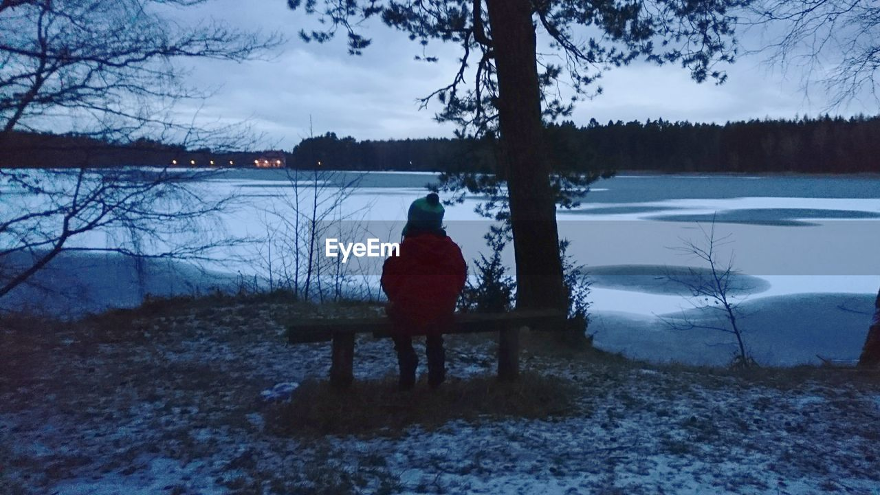 winter, snow, tree, lake, cold temperature, nature, rear view, solitude, one person, beauty in nature, weather, water, dusk, scenics, outdoors, tranquil scene, real people, tranquility, landscape, full length, sitting, bare tree, sky, silhouette, day, branch, warm clothing, people