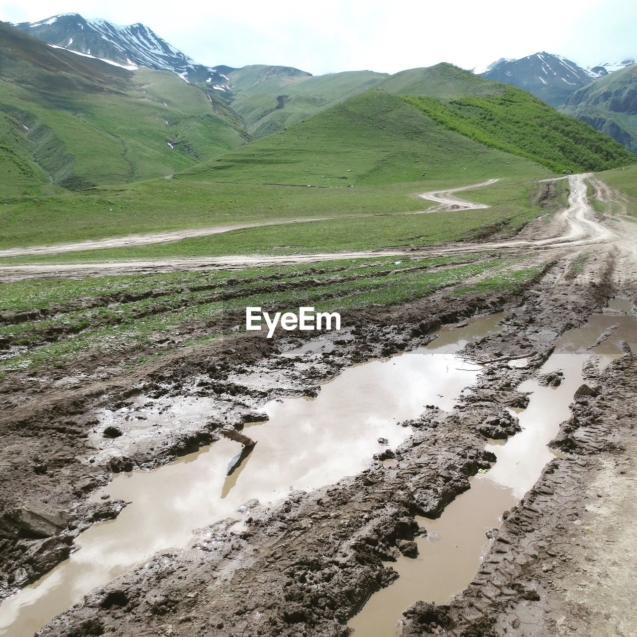 High Angle View Of Puddles On Dirt Road Leading Towards Mountains