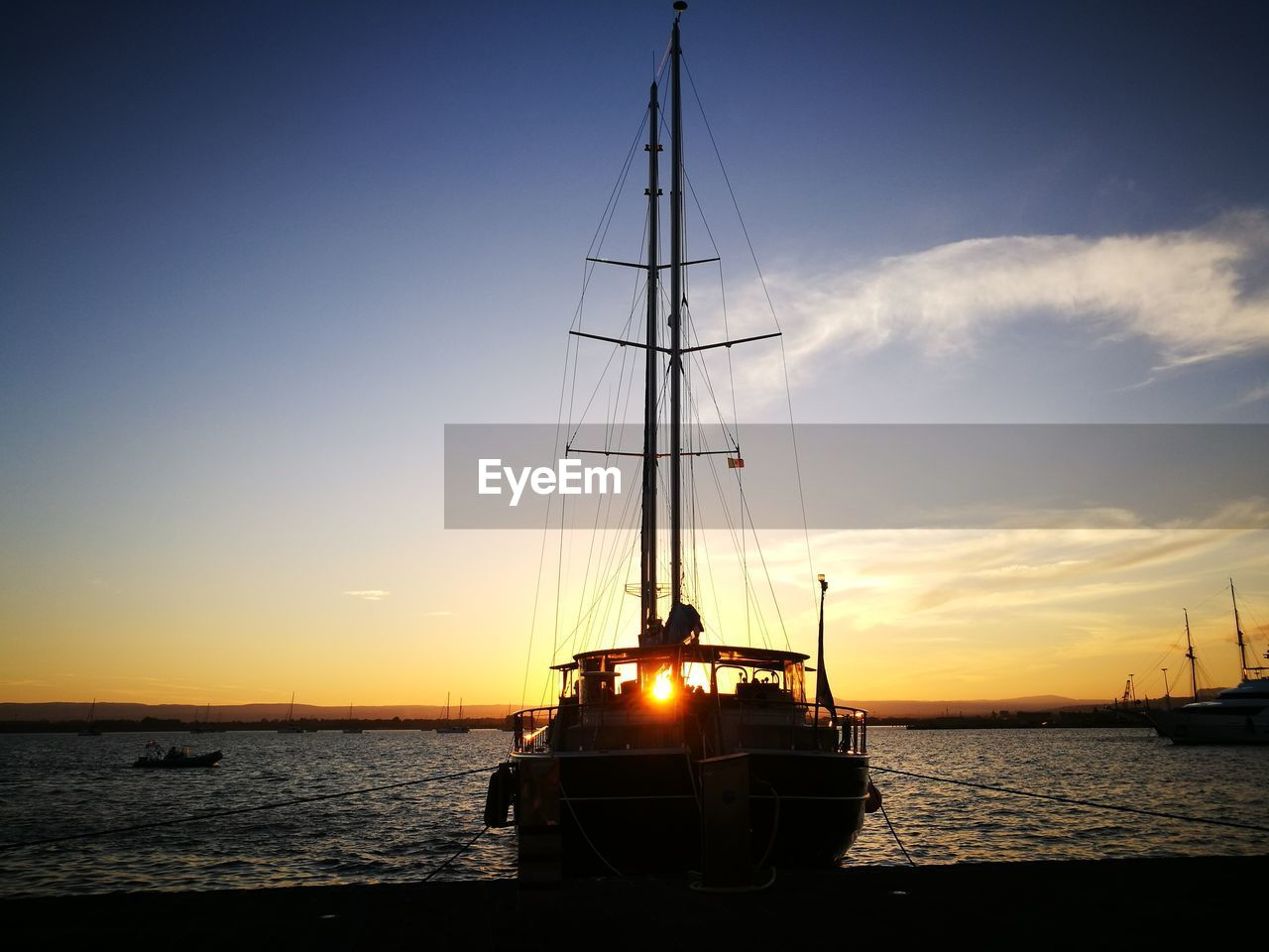 nautical vessel, water, sky, sunset, sea, transportation, mode of transportation, mast, sailboat, pole, beauty in nature, scenics - nature, sailing, nature, sun, silhouette, no people, ship, travel, outdoors, passenger craft, yacht