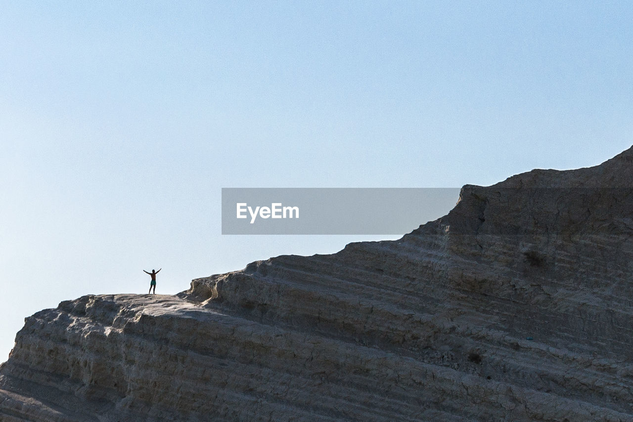Low Angle View Of Man Standing On Large Rock Against Clear Sky