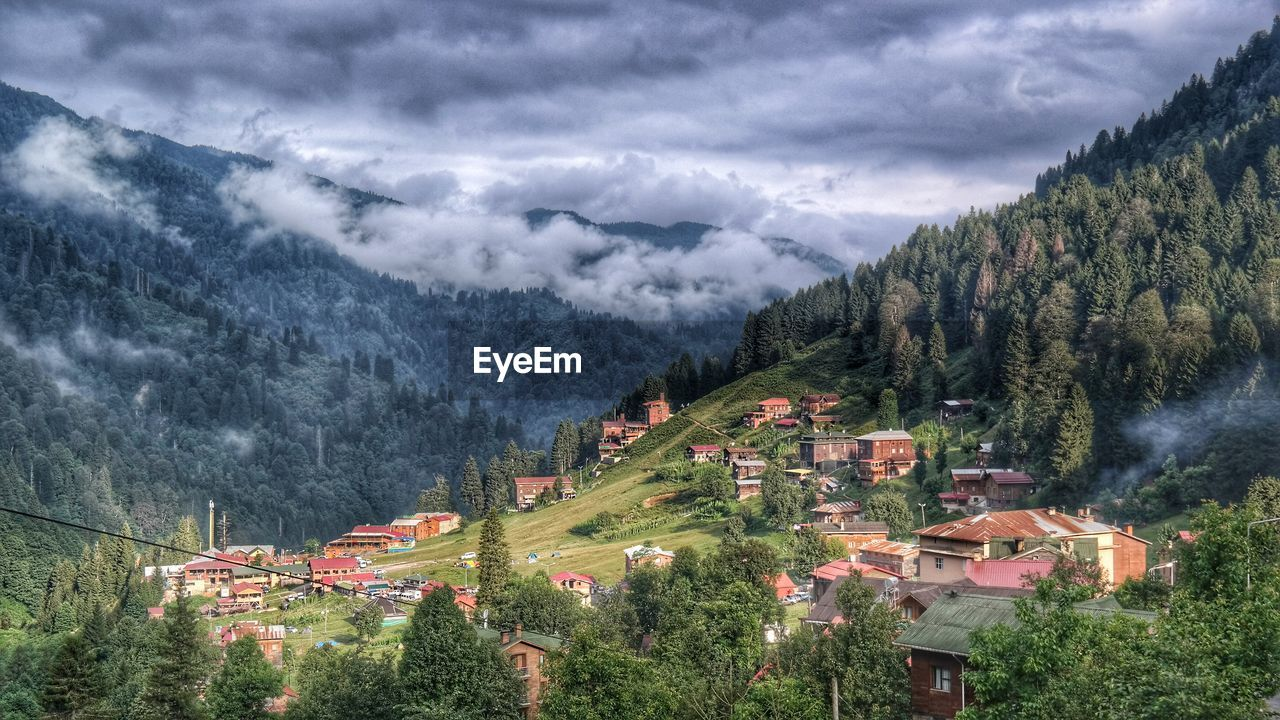 mountain, architecture, building exterior, cloud - sky, built structure, tree, sky, house, nature, high angle view, no people, scenics, beauty in nature, outdoors, tranquil scene, mountain range, tranquility, landscape, day, storm cloud