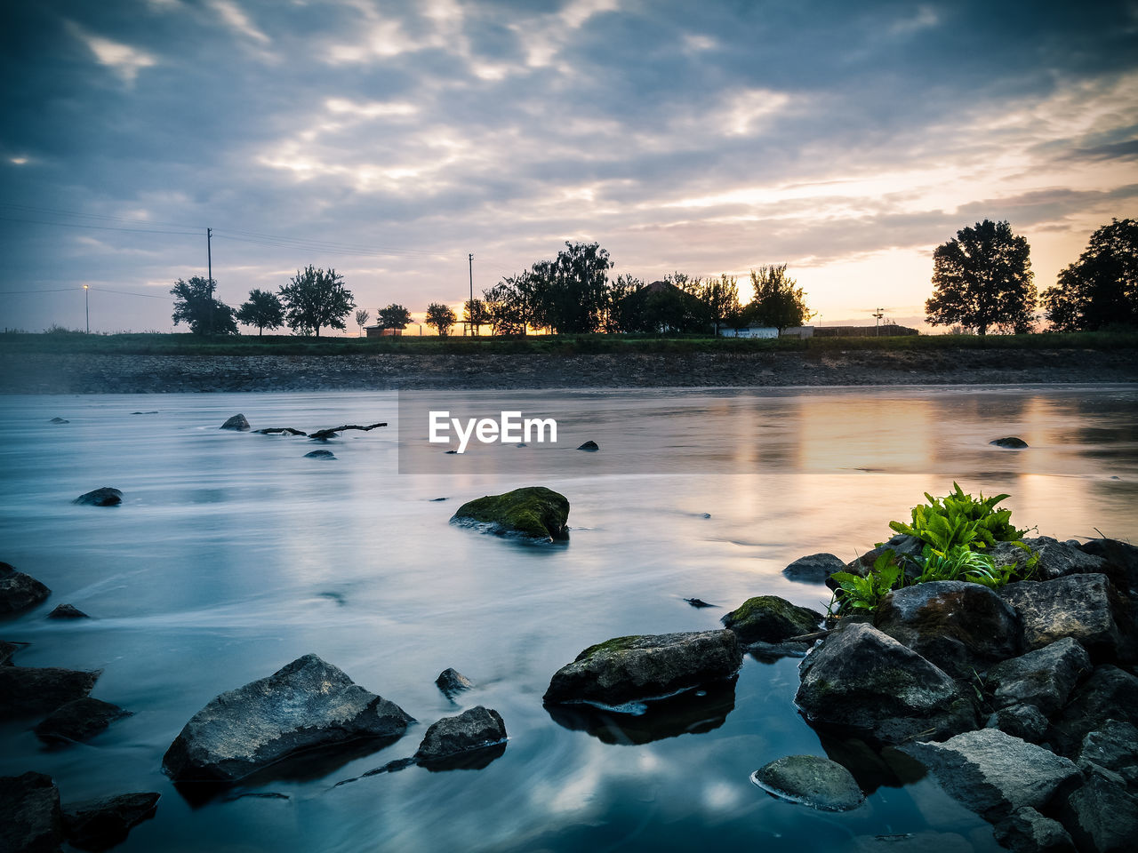 Scenic view of river against cloudy sky at sunrise