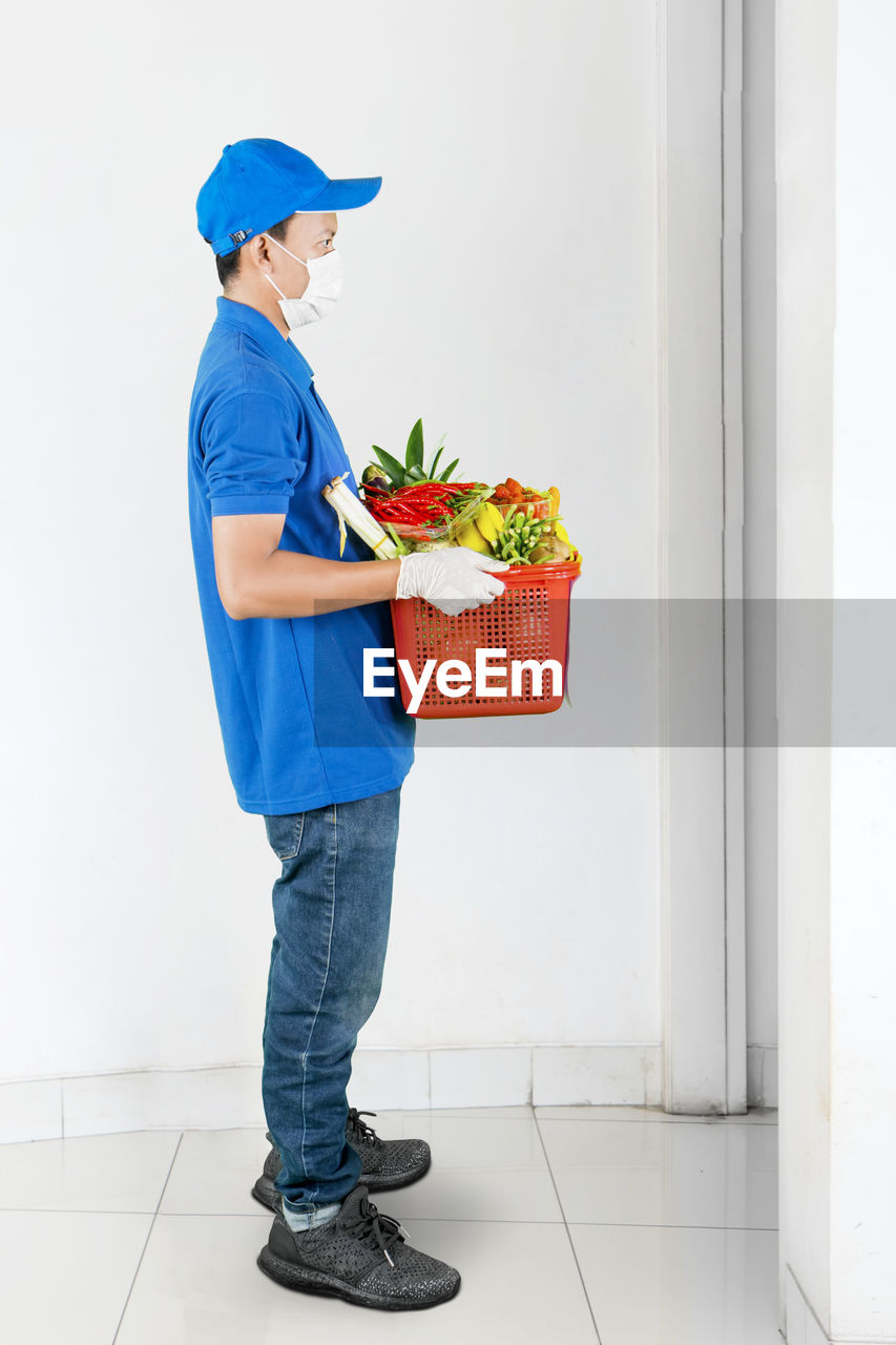 Full length of delivery person wearing mask holding fruits standing outdoors