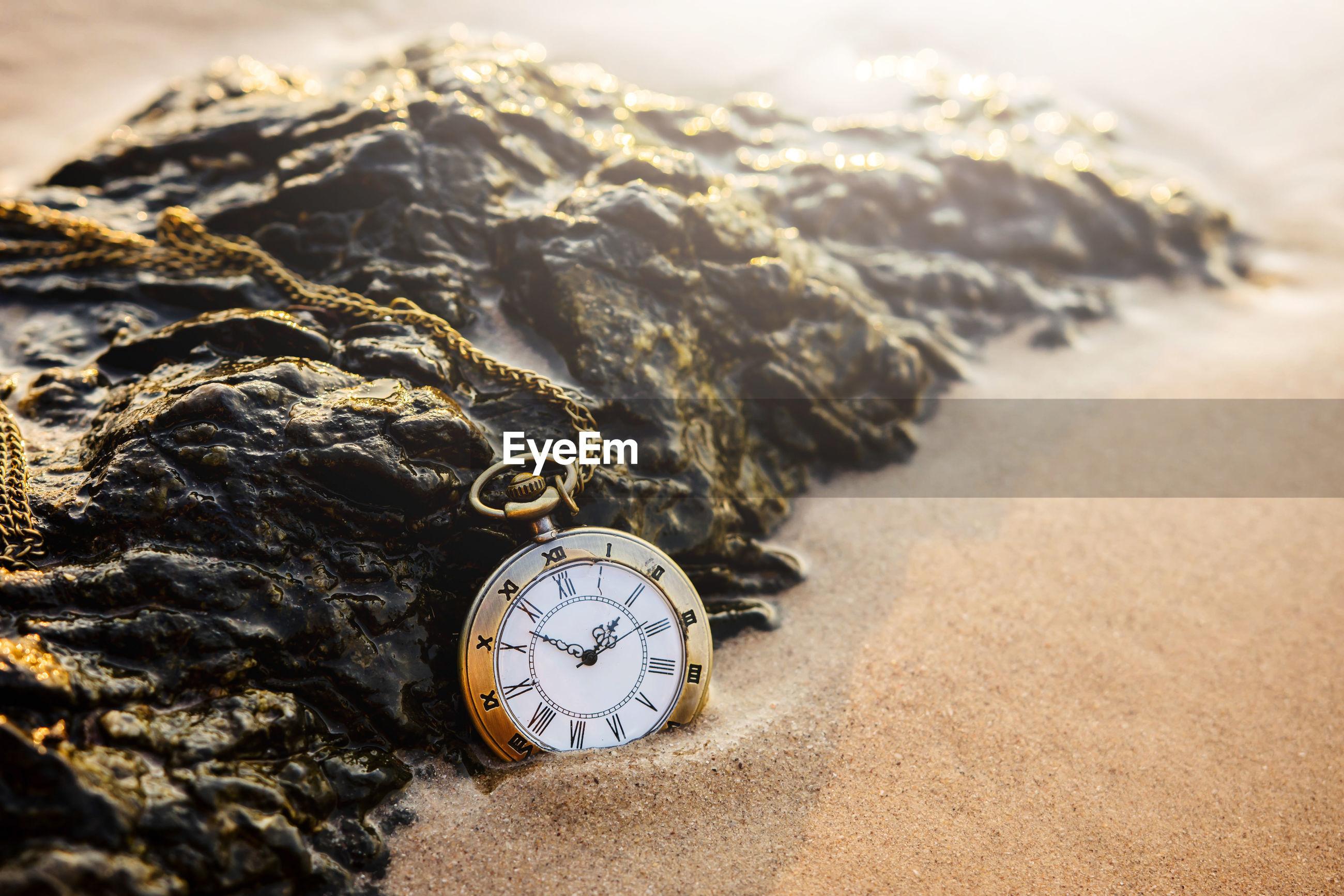 Close-up of clock pendant on sand
