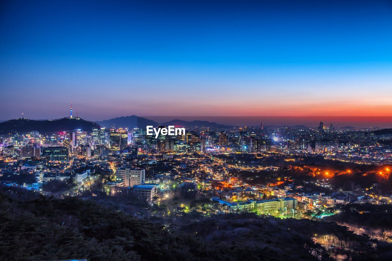 Aerial view of illuminated cityscape against blue sky during sunset
