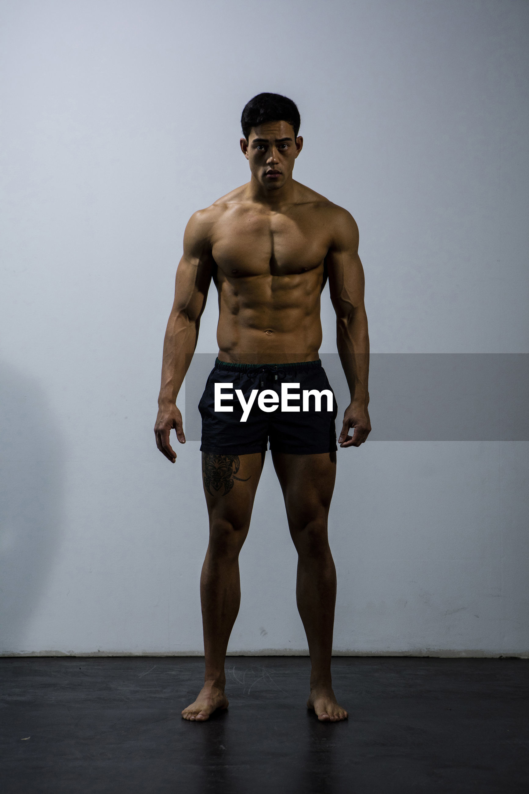 Portrait of shirtless muscular man standing against wall