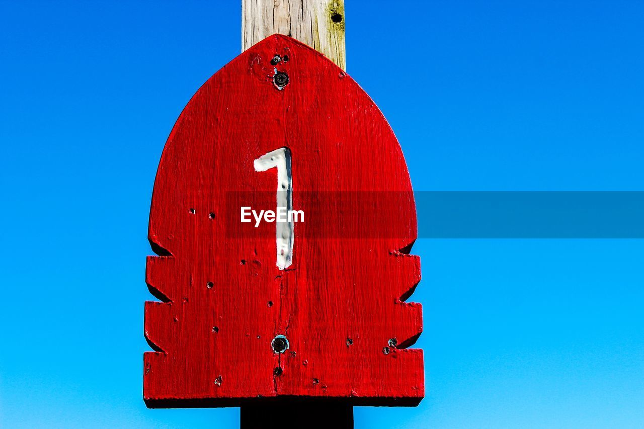 Number engraved on wooden plank against clear sky