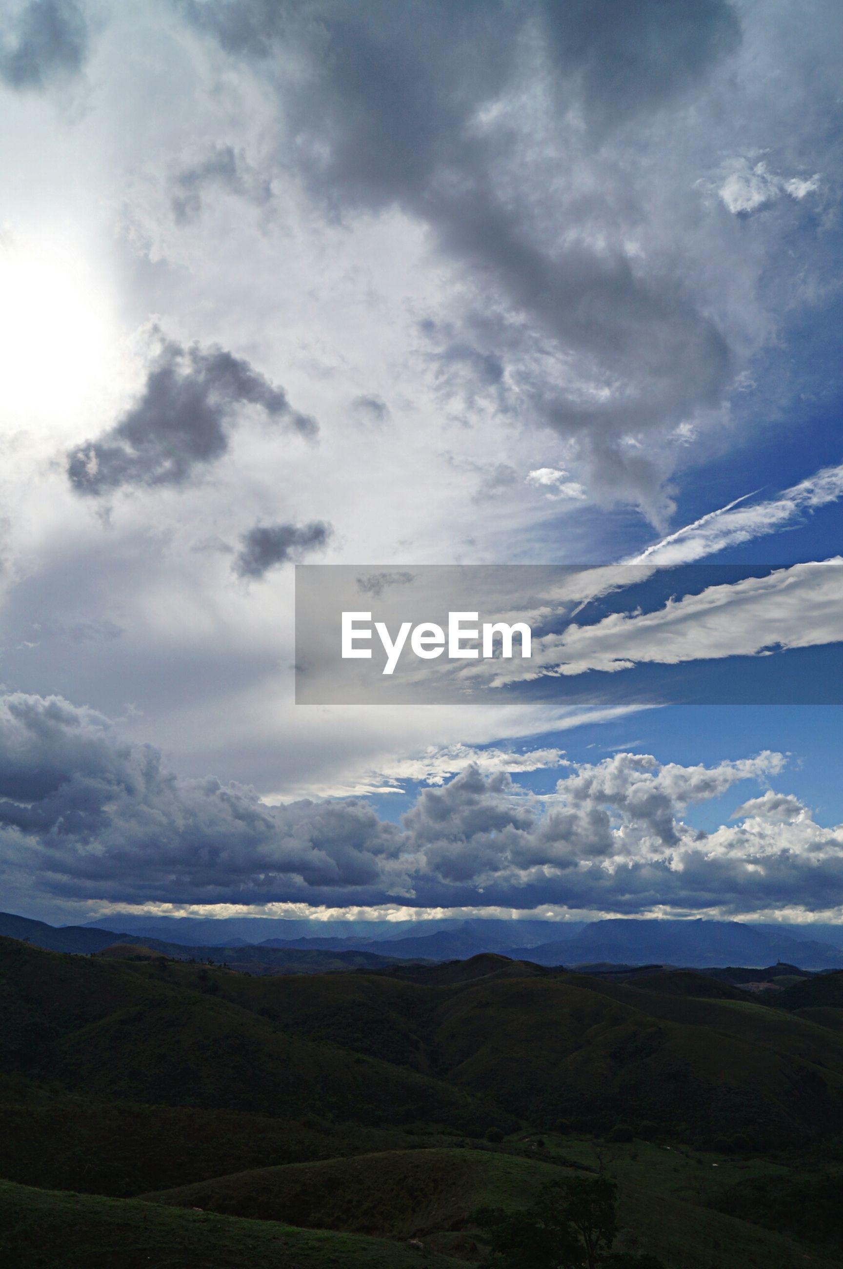 Clouds over dark hills