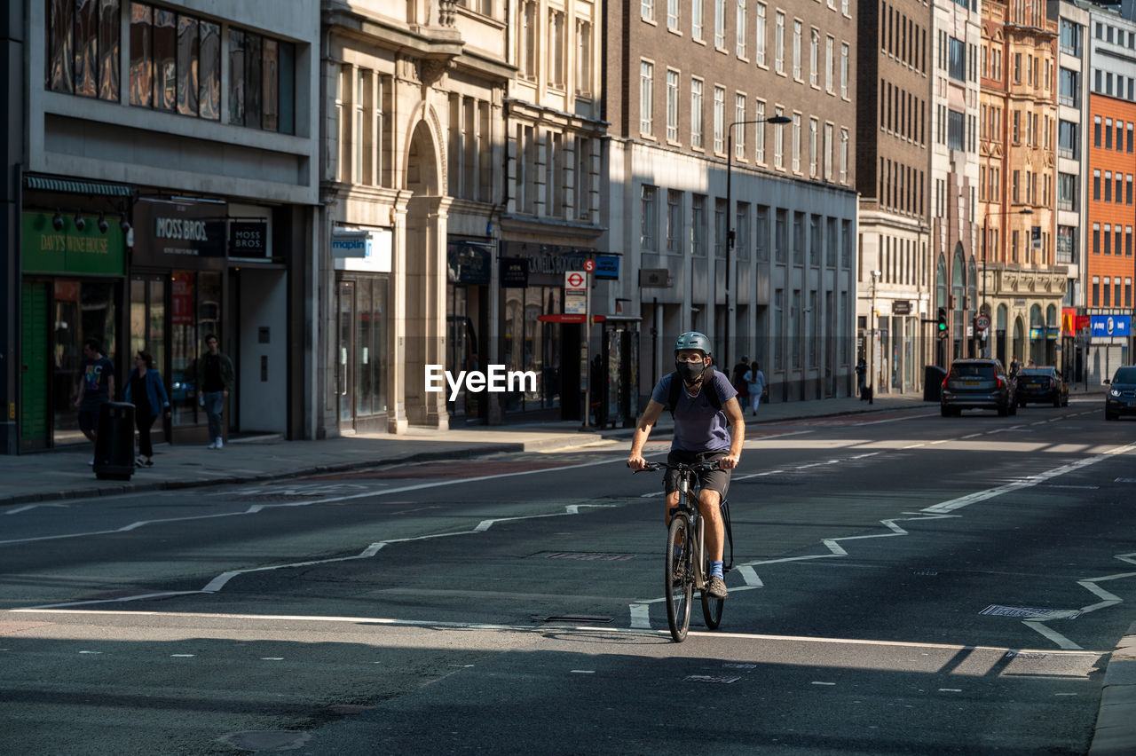 FULL LENGTH OF MAN RIDING BICYCLE ON STREET