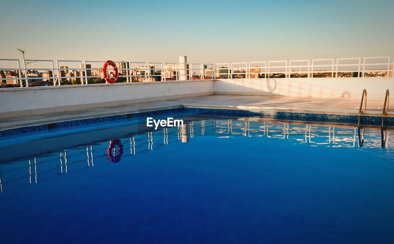water, swimming pool, blue, pool, architecture, nature, built structure, reflection, sky, waterfront, building exterior, clear sky, day, no people, outdoors, copy space, railing, city