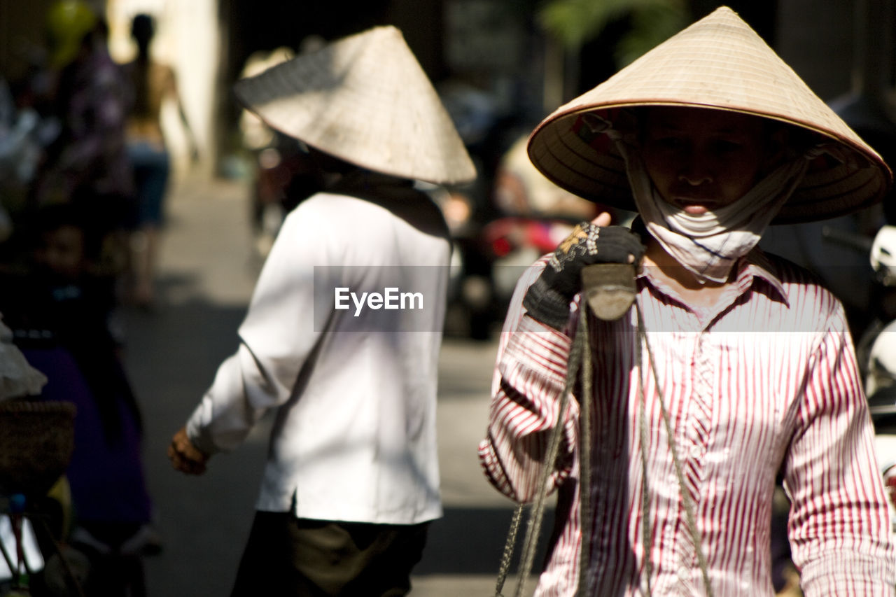 hat, real people, men, focus on foreground, outdoors, street, day, walking, rear view, lifestyles, asian style conical hat, togetherness, occupation, city, adult, people