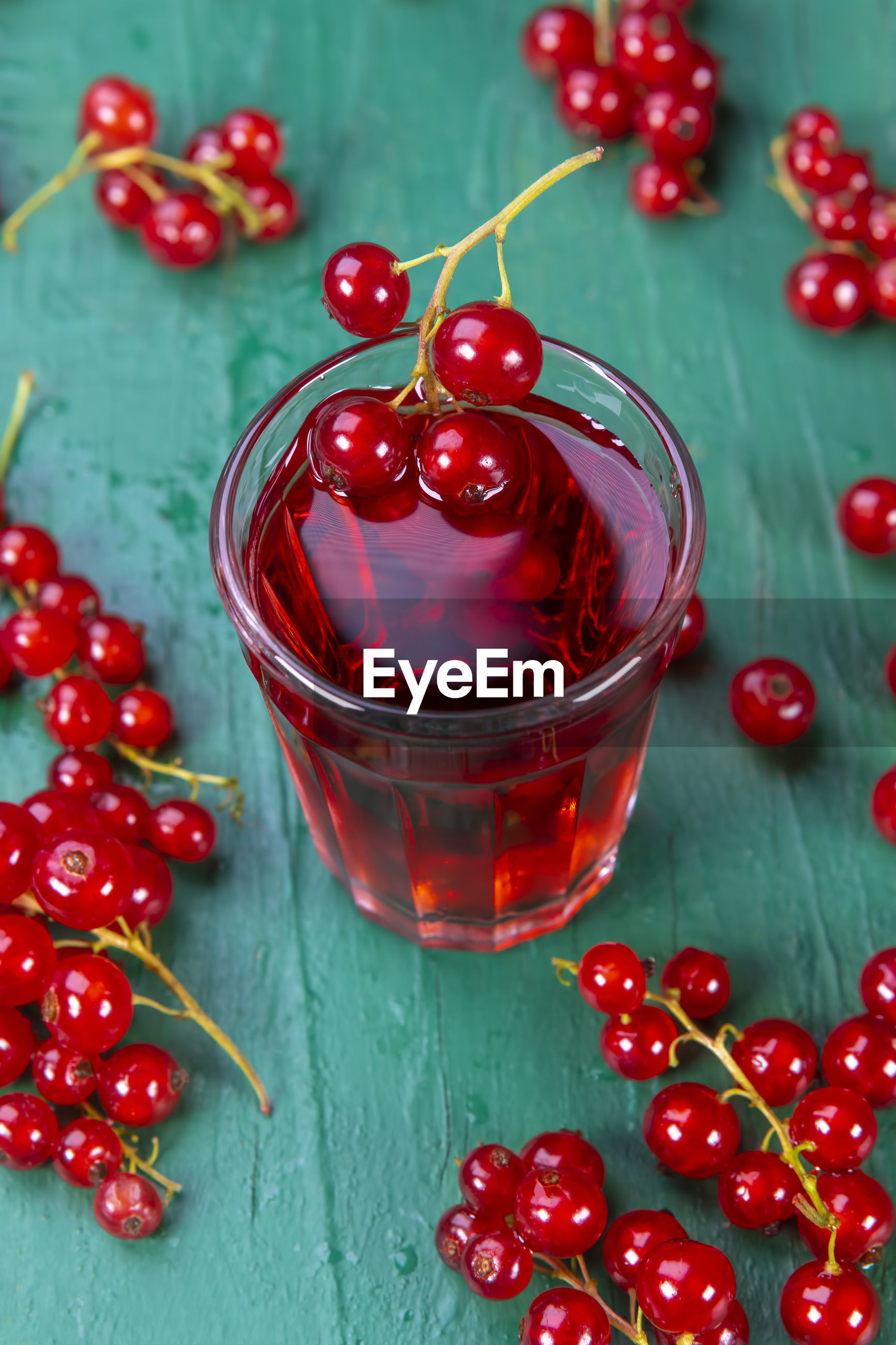High angle view of red currants with drink on wooden table