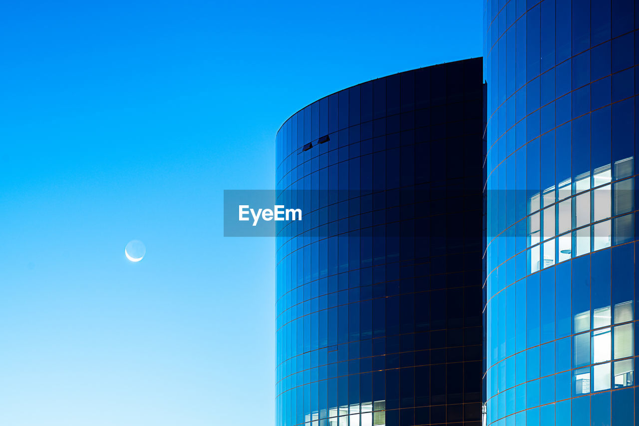 sky, blue, built structure, clear sky, low angle view, building exterior, moon, modern, nature, architecture, no people, outdoors, office building exterior, building, day, city, office, industry, sunlight, glass - material
