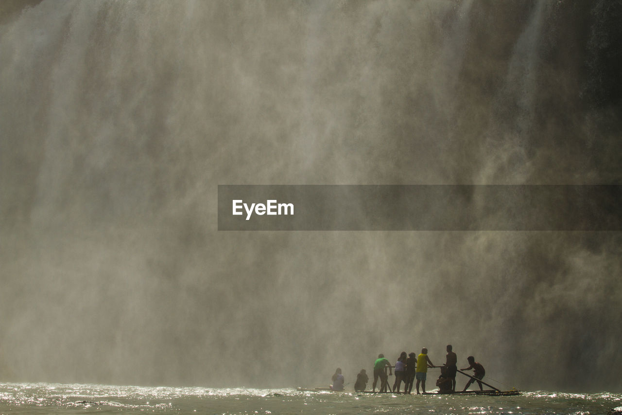 People standing against waterfall