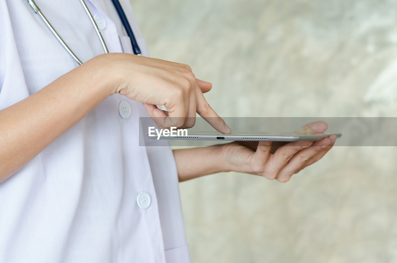 Midsection Of Female Doctor Using Digital Tablet Against Wall