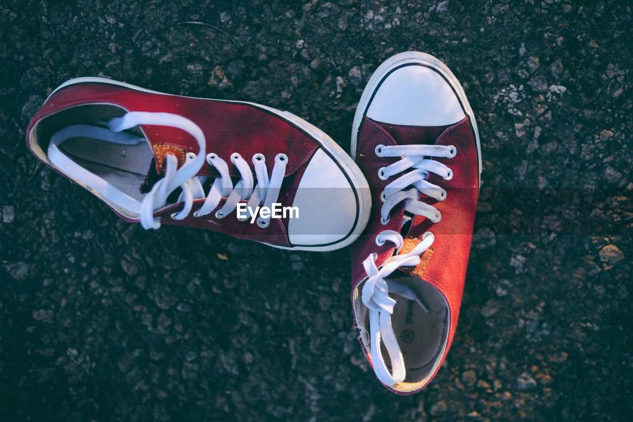 HIGH ANGLE VIEW OF CANVAS SHOES ON ROAD