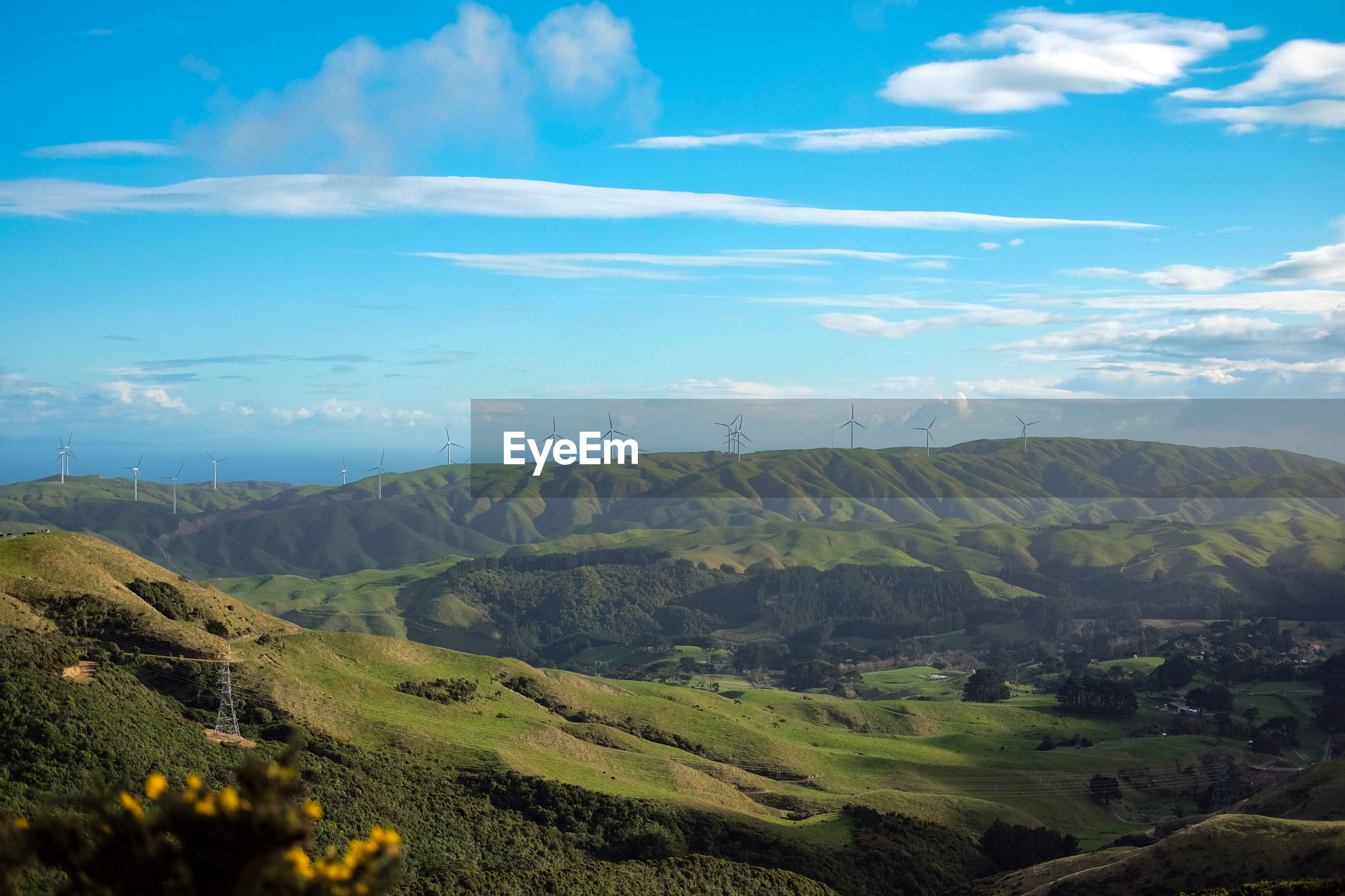 Wind turbines on the green rolling hills of new zealand. scenic view of landscape against sky.
