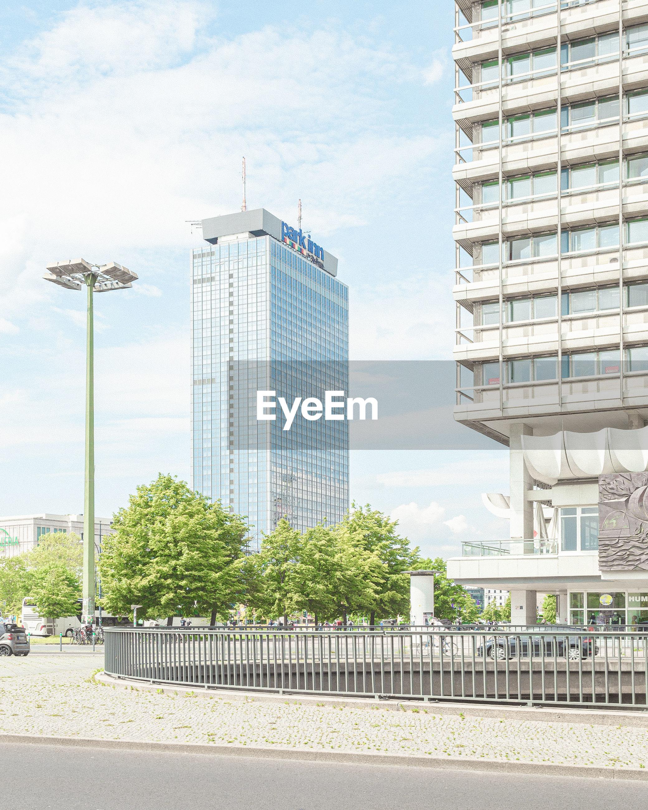 MODERN BUILDINGS BY STREET AGAINST SKY
