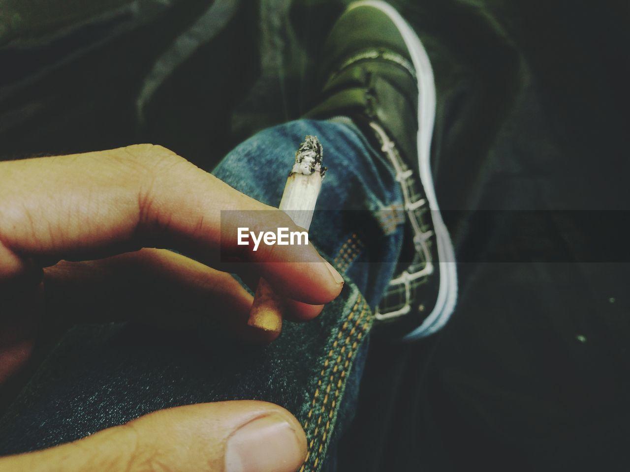 Cropped hand holding burning cigarette