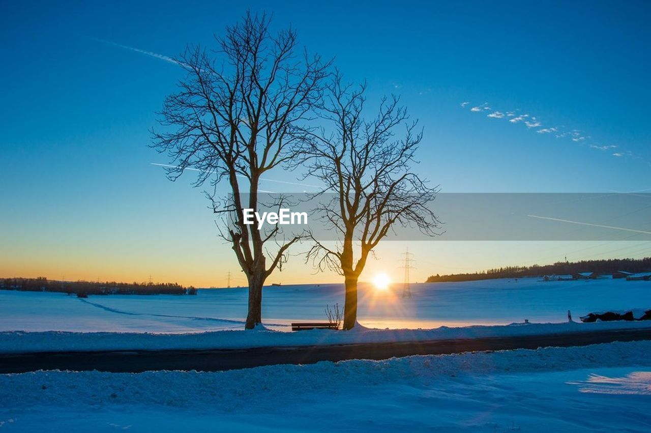 sunset, water, bare tree, tree, nature, beauty in nature, scenics, blue, sky, outdoors, winter, sea, cold temperature, tranquility, no people, branch, nautical vessel, clear sky, day, vapor trail