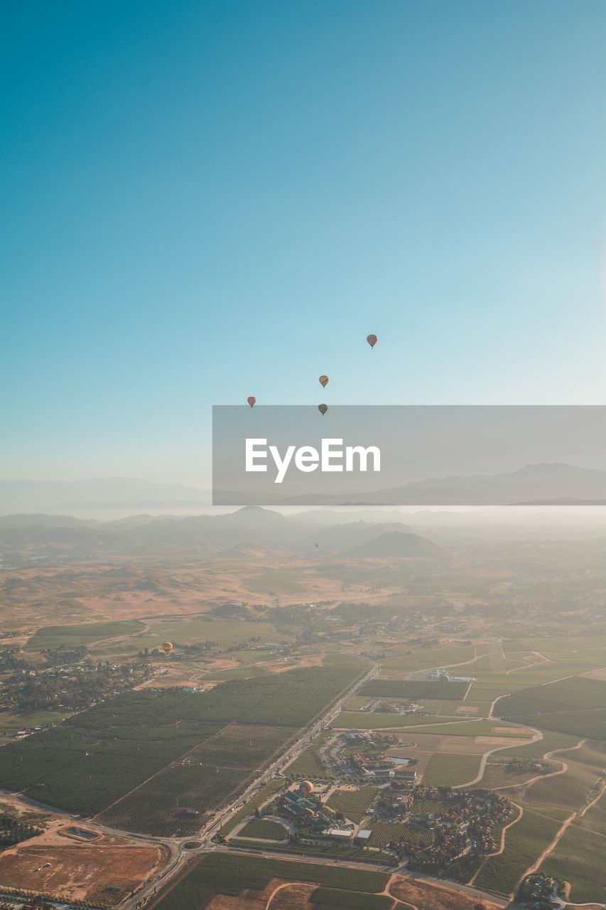 AERIAL VIEW OF HOT AIR BALLOON FLYING OVER LANDSCAPE