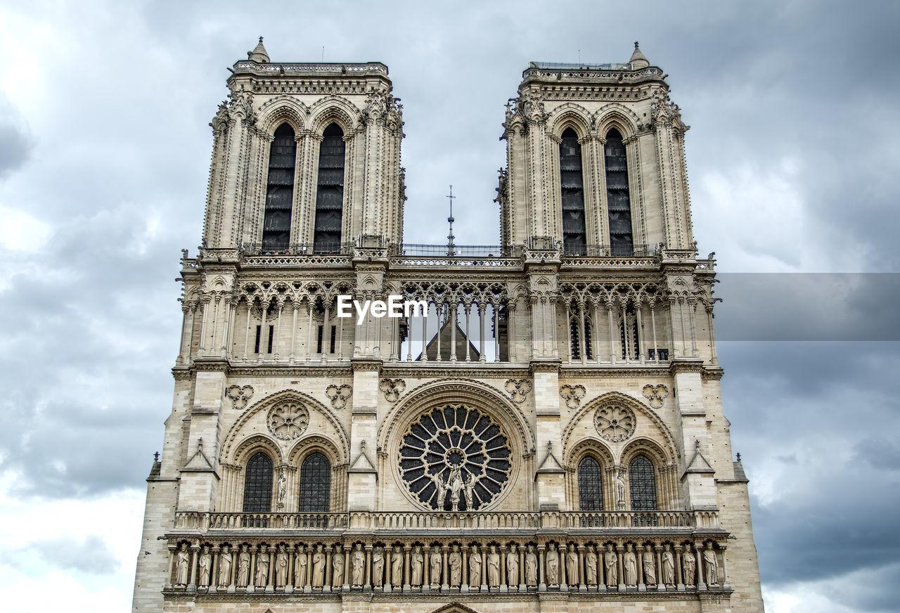 Low Angel View Of Notre Dame De Paris Against Cloudy Sky