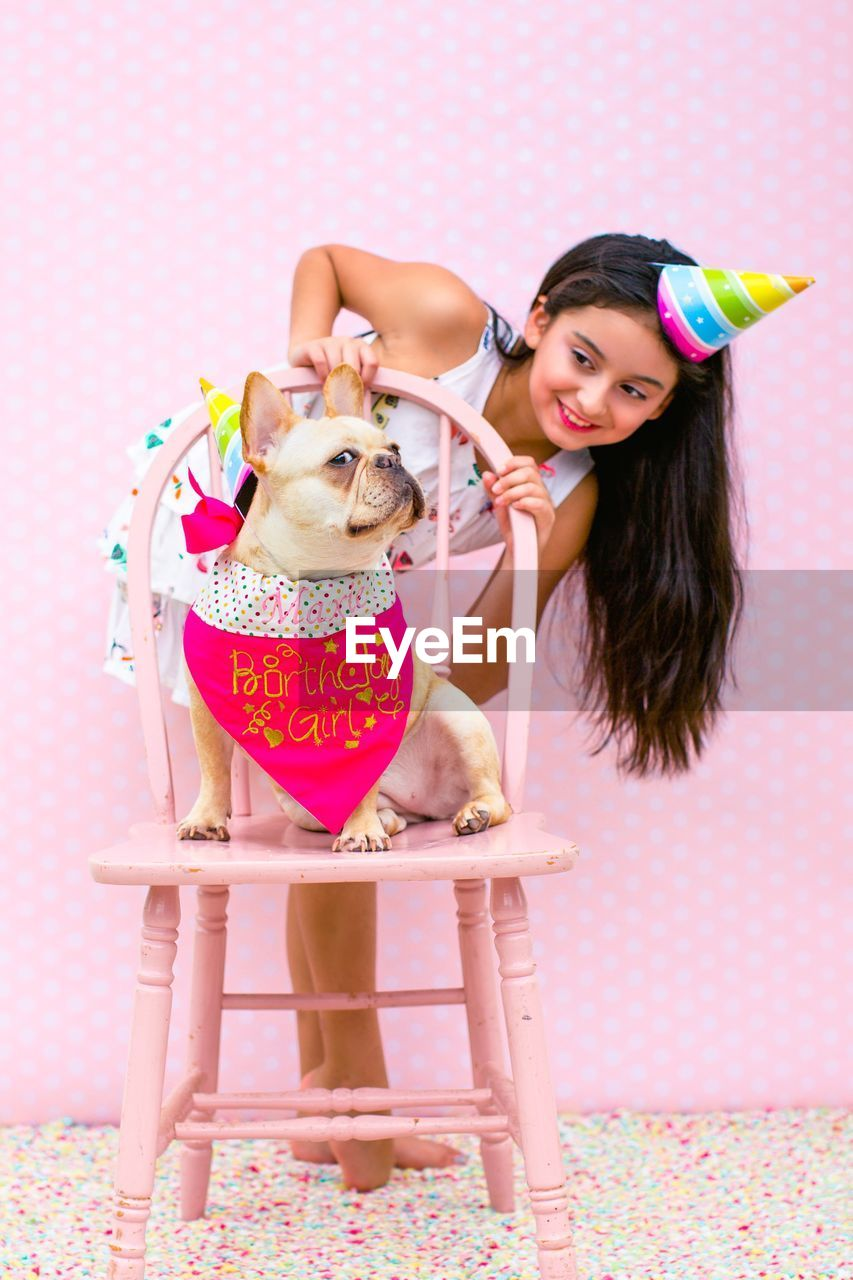 Cute girl looking at dog during birthday party at home