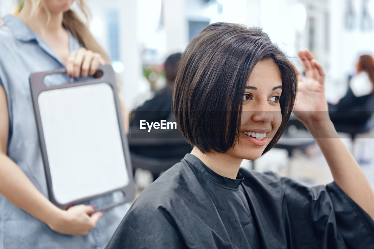 Beautician holding mirror for customer in salon