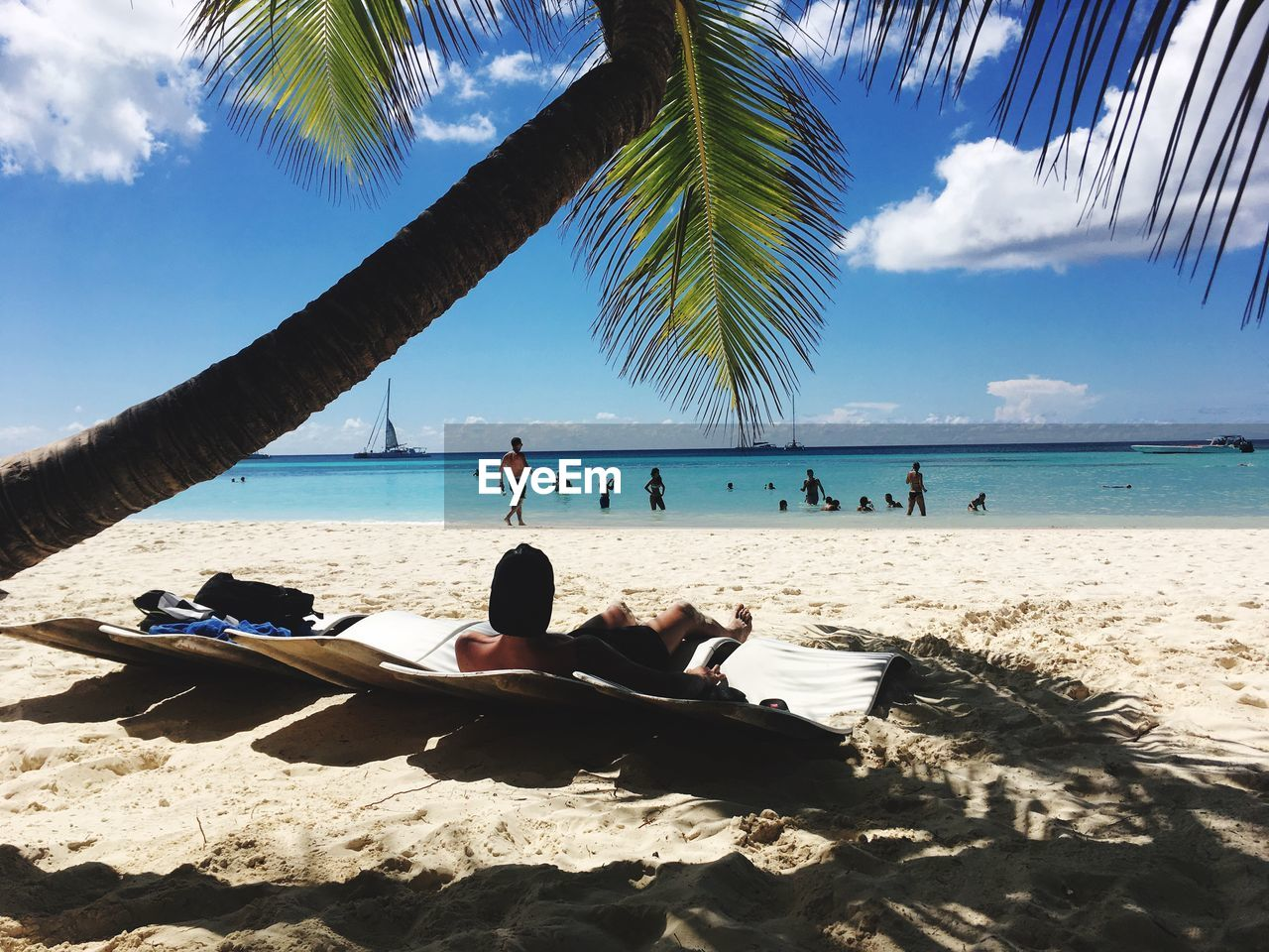 beach, land, sea, sky, water, tropical climate, palm tree, tree, sand, nature, beauty in nature, real people, leisure activity, sunlight, day, scenics - nature, horizon, holiday, lifestyles, horizon over water, outdoors, palm leaf