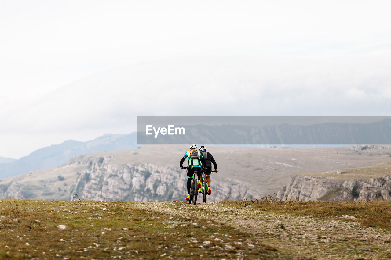 People riding bicycle on mountain against sky