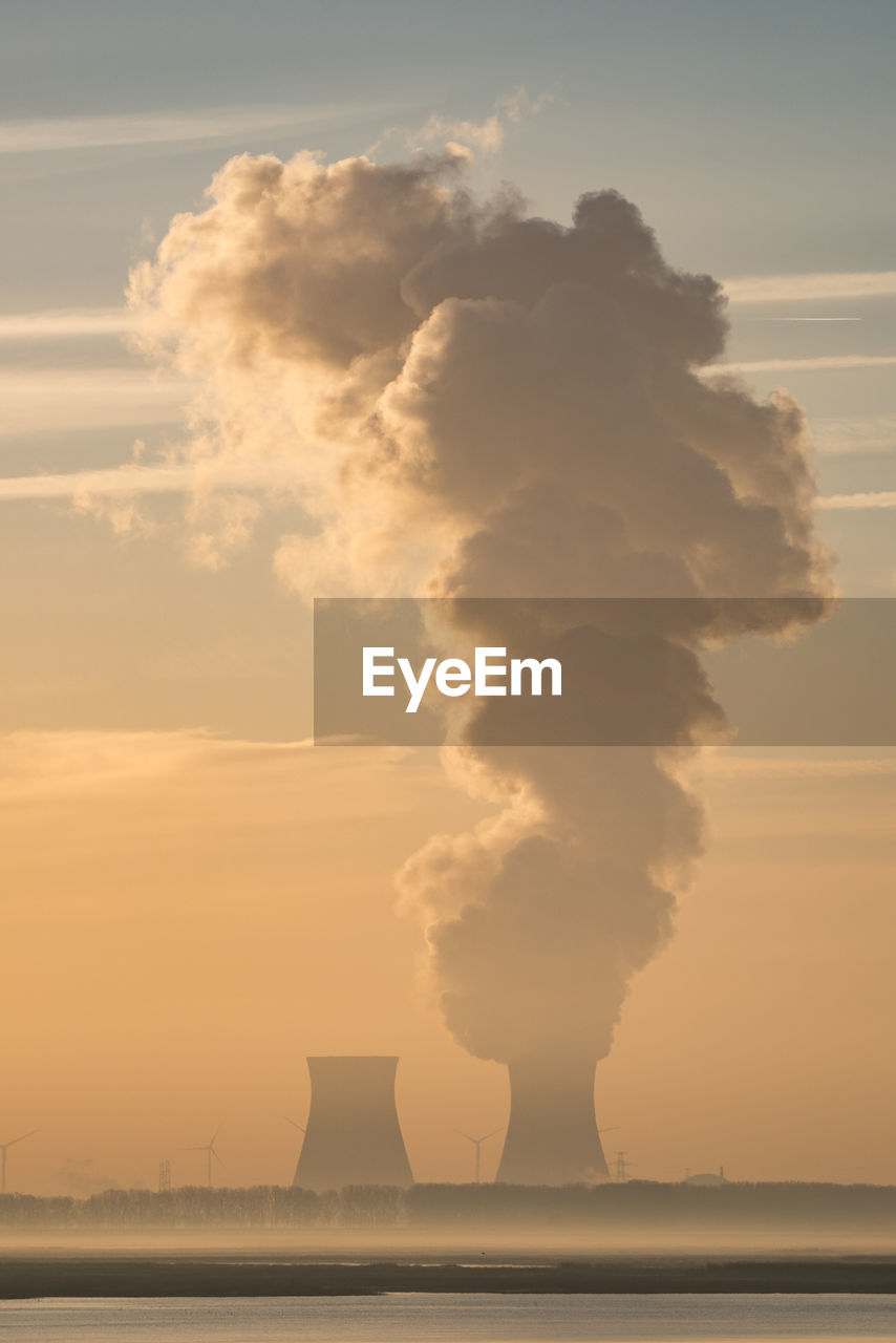Smoke emitting from nuclear power station against cloudy sky during sunset