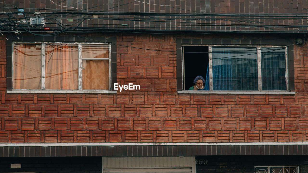 built structure, architecture, building exterior, window, building, day, brick wall, brick, wall, residential district, outdoors, people, real people, low angle view, glass - material, reflection, lifestyles, city, women