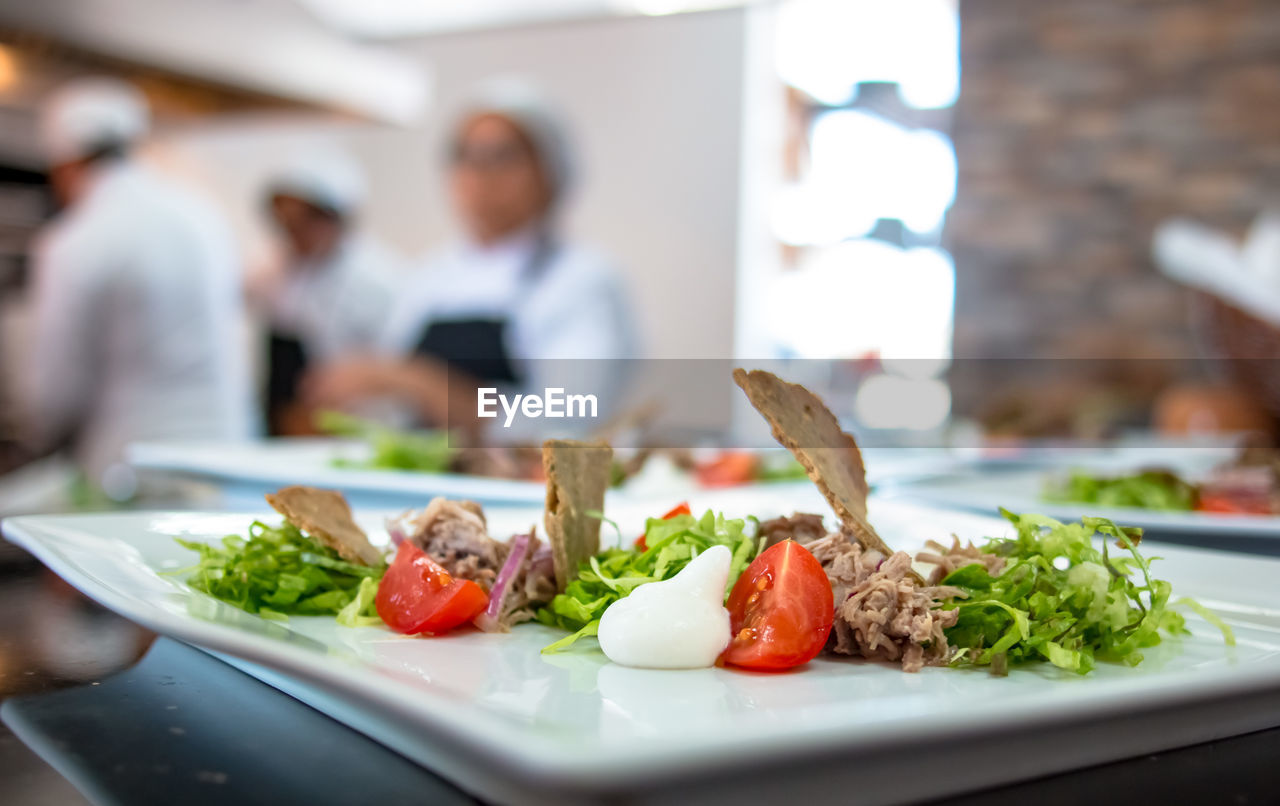 food, food and drink, healthy eating, vegetable, focus on foreground, freshness, indoors, plate, close-up, chef, commercial kitchen, real people, ready-to-eat, one person, day, people