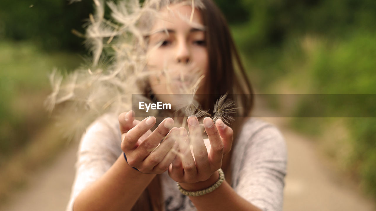 Close-up of woman blowing dandelion seeds