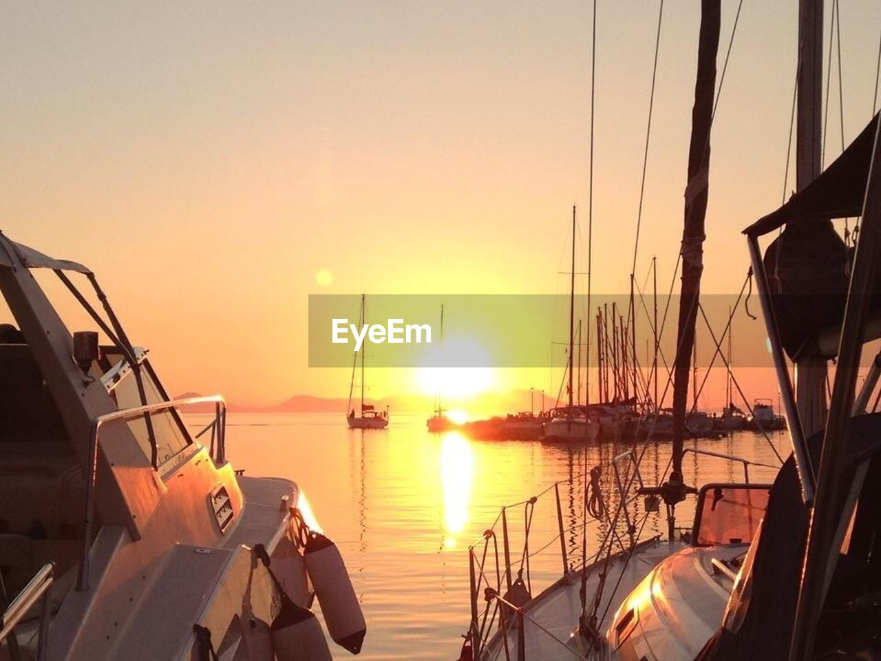 sunset, transportation, nautical vessel, reflection, mode of transport, moored, nature, boat, sunlight, orange color, tranquility, beauty in nature, sky, water, sun, scenics, tranquil scene, outdoors, harbor, mast, sea, no people, sailboat, yacht, day