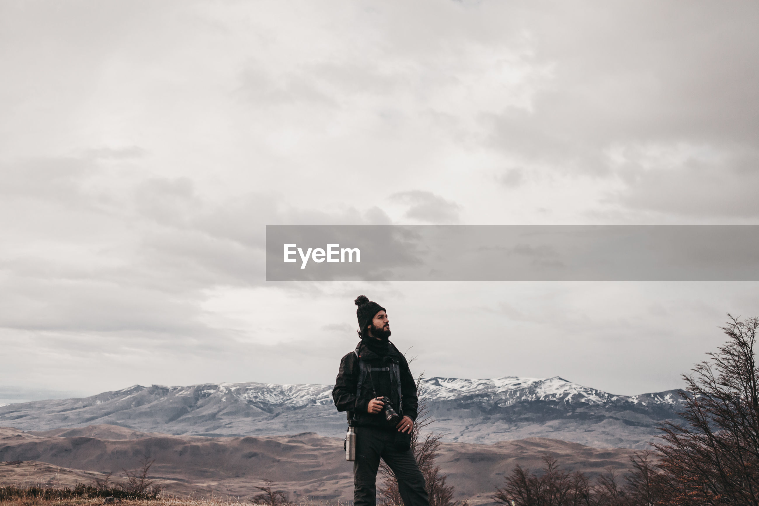 MAN STANDING ON MOUNTAINS AGAINST SKY