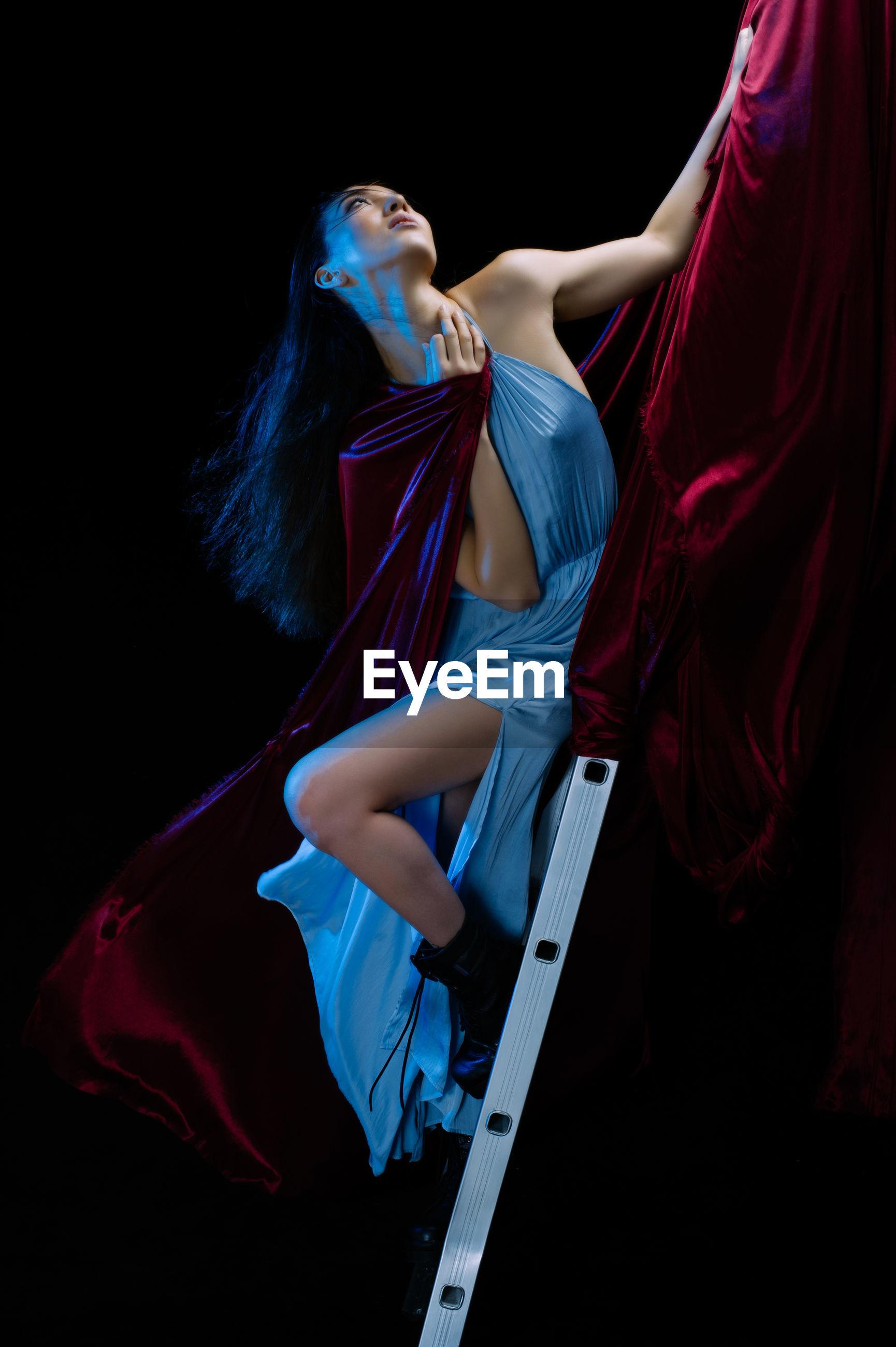 Glamorous woman posing on ladder