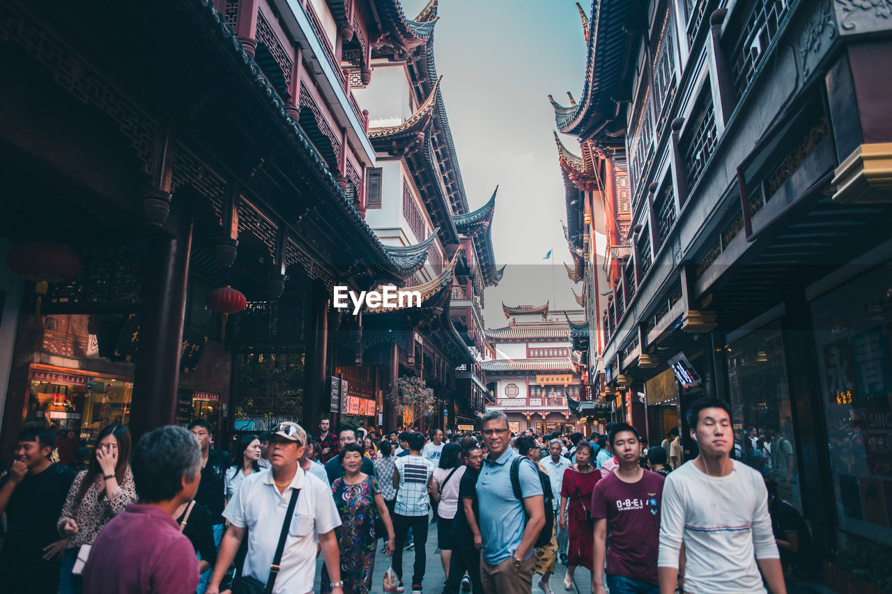 real people, men, built structure, group of people, architecture, building exterior, lifestyles, large group of people, crowd, city, women, adult, market, street, building, illuminated, casual clothing, leisure activity, shopping, outdoors