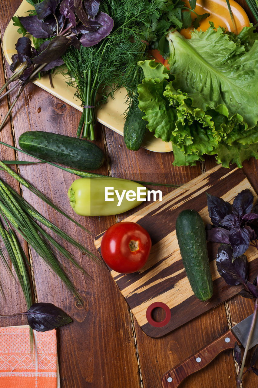 food and drink, food, vegetable, healthy eating, wellbeing, freshness, fruit, cutting board, indoors, high angle view, no people, wood - material, green color, table, kitchen knife, choice, variation, still life, preparation, directly above, herb, chopped