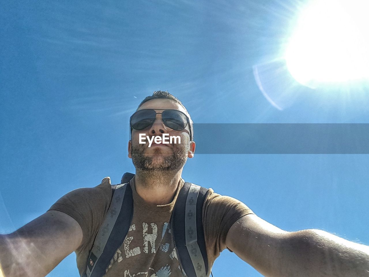 sunglasses, front view, sunlight, young adult, low angle view, real people, blue, day, leisure activity, young men, selfie, sky, one person, lifestyles, outdoors, portrait, young women
