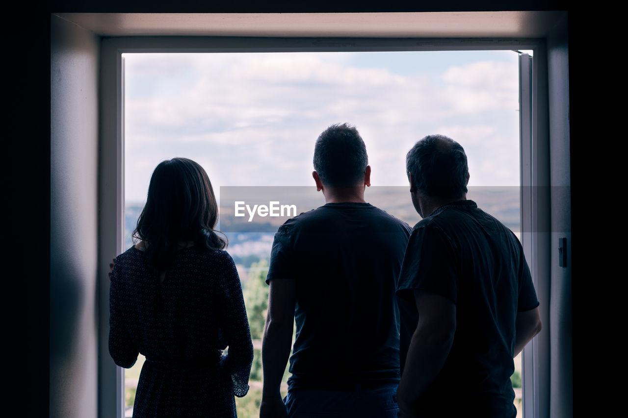Rear View Of People Standing At Doorway