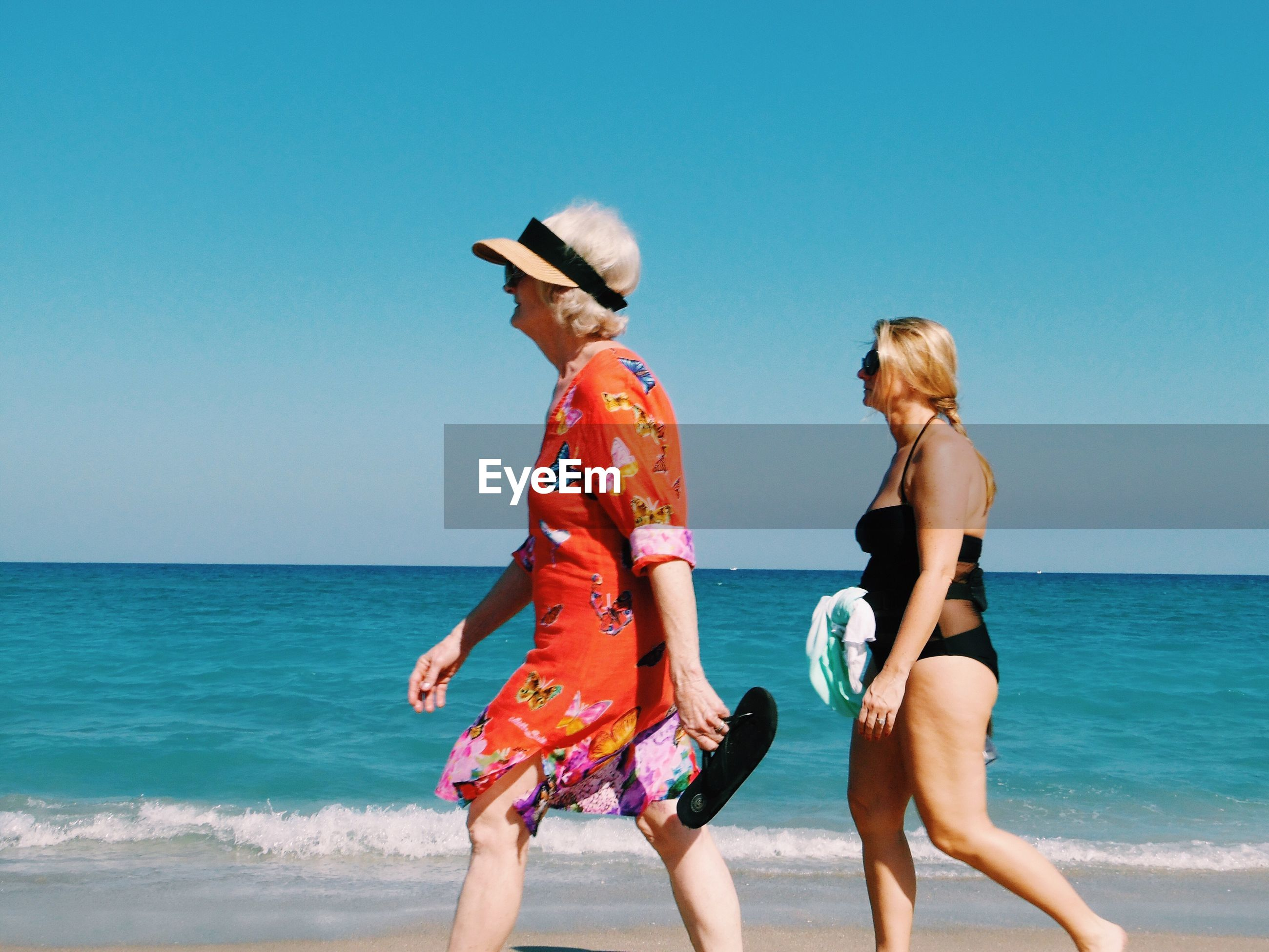 REAR VIEW OF FRIENDS STANDING ON BEACH AGAINST CLEAR BLUE SKY