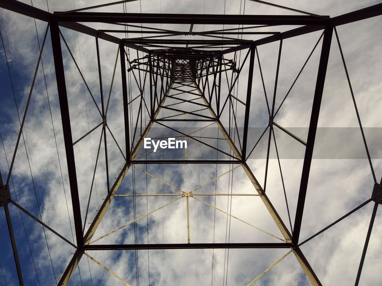sky, built structure, low angle view, cloud - sky, architecture, nature, connection, no people, electricity pylon, metal, technology, fuel and power generation, electricity, outdoors, day, tall - high, pattern, directly below, power supply, cable, girder